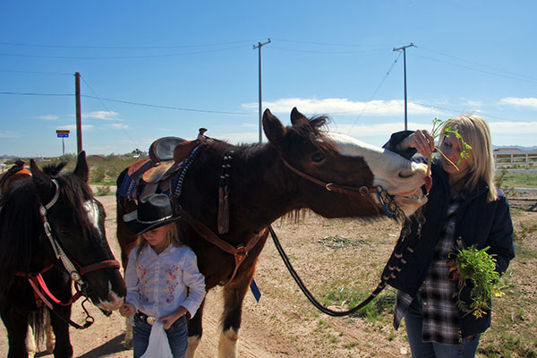 A young lady and her mother ride up on horses to Tonopah Rob's Vegetable Stand in Tonopah, Arizona